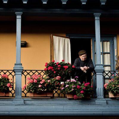 Imagen de una persona de la tercea edad asomada al balcón